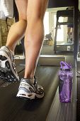 man's muscular legs on treadmill, closeup