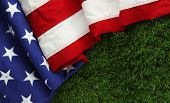 Red, white, and blue American flag on grass for Memorial Day or Veterans day background poster