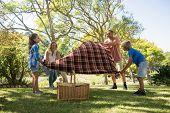 Family spreading the picnic blanket in park poster