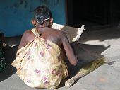 Old Woman Threshes Grain