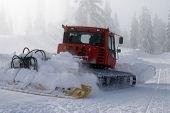 A snowplow prepares a run at a ski resort.