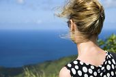 A blonde woman looking out to sea from the top of a hill on a windy day.