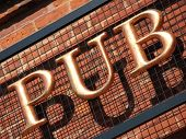 A three-dimensional metal PUB sign in a serif typeface.