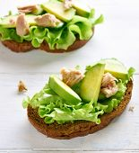 Close Up Of Tuna Sandwiches With Avocado And Lettuce Leaves On Light Wooden Table. Tasty Tuna Sandwi poster