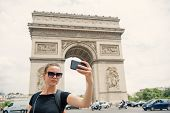 Woman With Smartphone At Arch Monument In Paris, France. Woman Make Selfie With Phone At Arc De Trio poster