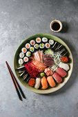 Sushi Set Nigiri Sashimi And Sushi Rolls In Ceramic Serving Plate With Salad, Soy Sauce And Chopstic poster