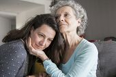 Content Elderly Woman And Her Daughter Embracing. Mother And Daughter Sitting On Couch With Home Int poster