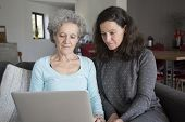 Serious Senior Woman And Her Daughter Using Laptop Computer. Mother And Daughter Sitting On Couch Wi poster