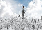 Confident Businessman In Suit Standing On Pile Of Documents Among Flying Letters With Cloudly Skysca poster