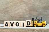 Toy Forklift Hold Letter Block D To Complete Word Avoid On Wood Background poster