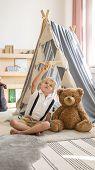 Cute Little Blonde Boy Sitting Next To Teddy Bear In Stylish Scandinavian Kids Playroom poster