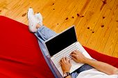 image of futon  - A man sitting on a red couch working on a laptop computer - JPG