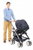 Full length portrait of a young male pushing a baby stroller isolated on white background