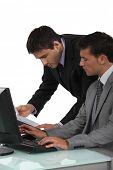 dupla de executivos masculinos trabalhando no laptop