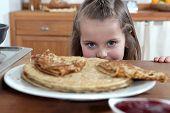 Greedy girl looking at pancakes