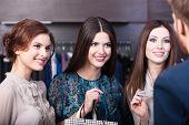 Three girlfriends talk with salesperson