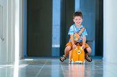Lindo niño feliz con una maleta en el aeropuerto