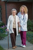 Nurse Helping Senior Walking with Cane Outdoor in Early Morning Outside House