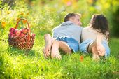 Happy Couple Relaxing on the Grass and Eating Apples in Autumn Garden.Healthy Food.Outdoor?.Park.Bas
