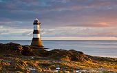 pic of early morning  - The lighthouse at Black Point on the Welsh coastline bathed in early morning sunlight - JPG