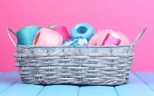 Bright threads in basket on wooden table on pink background
