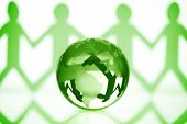 Paper chain men holding hands around a green globe concept for partnership, teamwork or global community