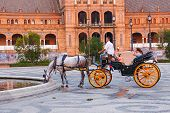 SEVILLA, SPAIN - JULY 19 : Tourists enjoy a trip on horsedrawn cart on Plaza de Espana, Seville on J