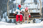 stock photo of lifting-off  - Mother And Daughter Getting Off chair Lift On Ski Holiday In Mountains - JPG
