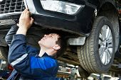 automotive mechanic worker examining car bottom during automobile car maintenance at lever repair se