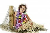 An elementary girl in flower leis and a grass skirt resting against fish-net covered posts.  On a white background.