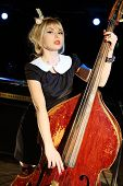 Beautiful woman in black dress plays old contrabass in night club.