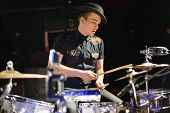 Handsome young man in hat plays drum set in night club.