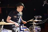 Young man in hat and black shirt plays drum set in night club.