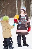 Older girl gives eskimo made of snow in plastic bucket and broken branch to younger child in winter