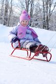 stock photo of toboggan  - Happy little girl in pink scarf and hat goes tobogganing on snow in winter - JPG