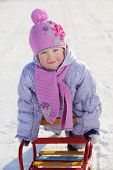 Warmly dressed smiling girl in pink scarf and hat relies on sled in winter.