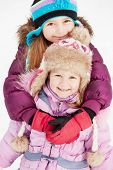 Older girl embraces her younger sister from behind standing on snow background