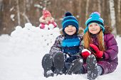 Smiling boy and girl sit nearby on snow and little girl in background builds wall of snow blocks