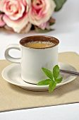 a cup of espresso with stevia leaves