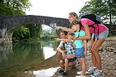 Family on a hiking journey standing by the river