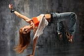 stock photo of break-dance  - modern style dancer posing behind studio background - JPG