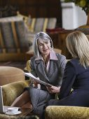 Two businesswomen with documents sitting in office lobby