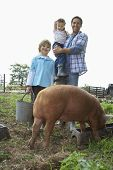Full length portrait of a happy father and children with pig in sty against clear sky