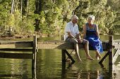 Full length of happy senior couple sitting on pier at lake