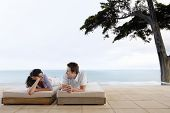 stock photo of infinity pool  - Happy young couple looking at each other while relaxing on sunbeds by infinity pool - JPG