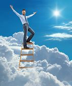 young confident businessman standing at the ladder high in the sky spread his arms