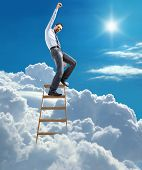 stock photo of main idea  - young man in shirt and tie pulls his hand up to the sky on top of the ladder on heaven - JPG