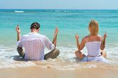 foto of middle finger  - Happy young couple showing middle finger and enjoying at beach with blue sea on background - JPG