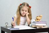 The girl writes on a piece of paper sitting at the table in the image of the writer