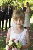 Portrait of cute little bridesmaid holding bouquet in garden with guests and wedding couple in background